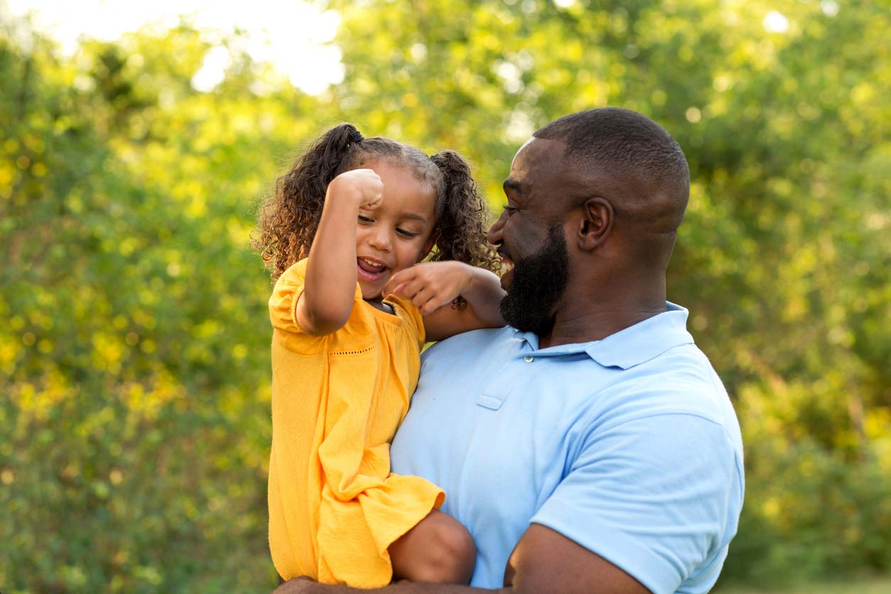 Dad holding daughter doing strong arm