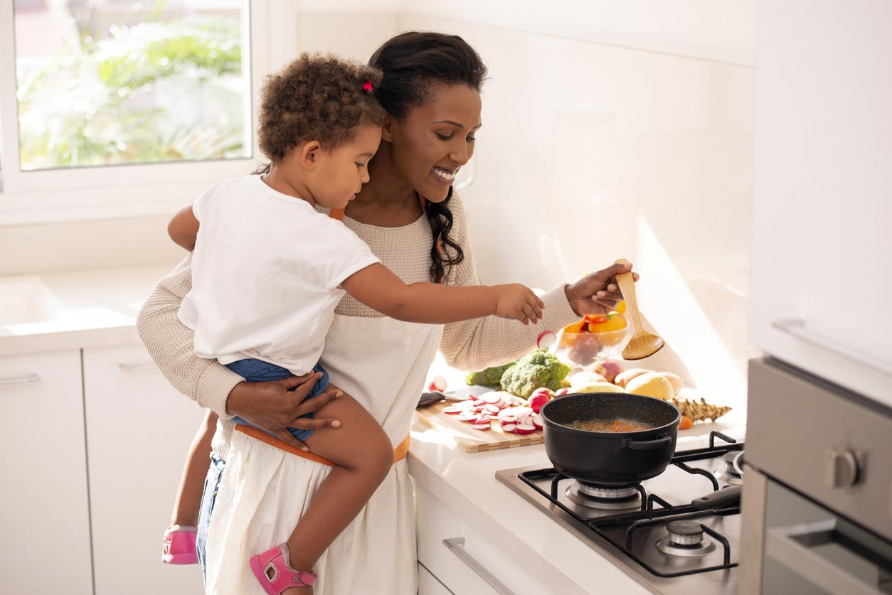 mother and daughter cooking soup
