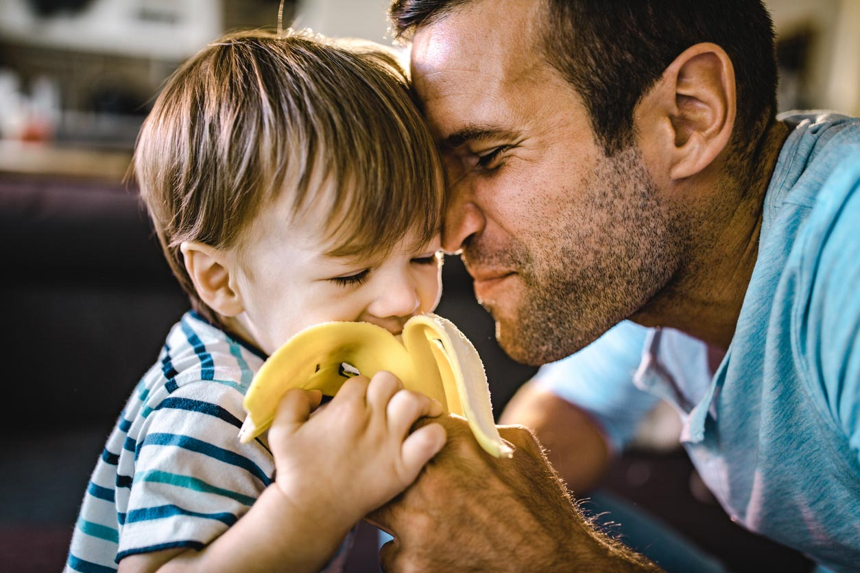 father feeding boy with banana