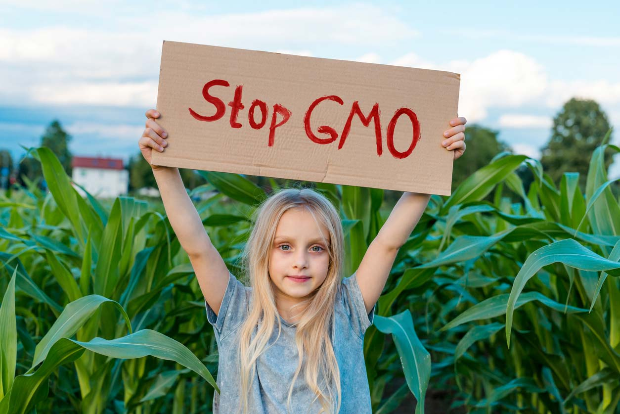 small girl holding stop gmo sign