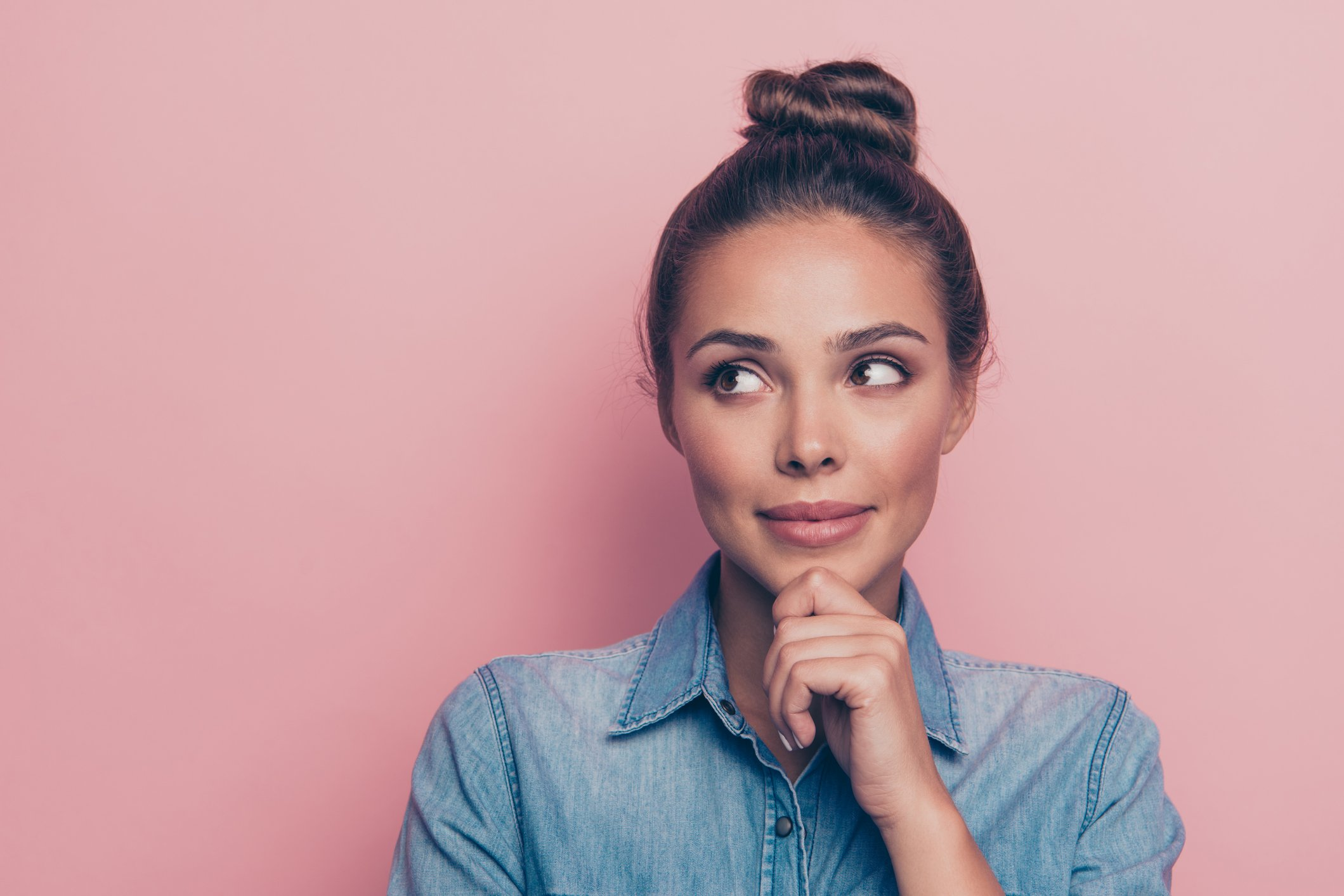 Portrait of curious woman on pink background
