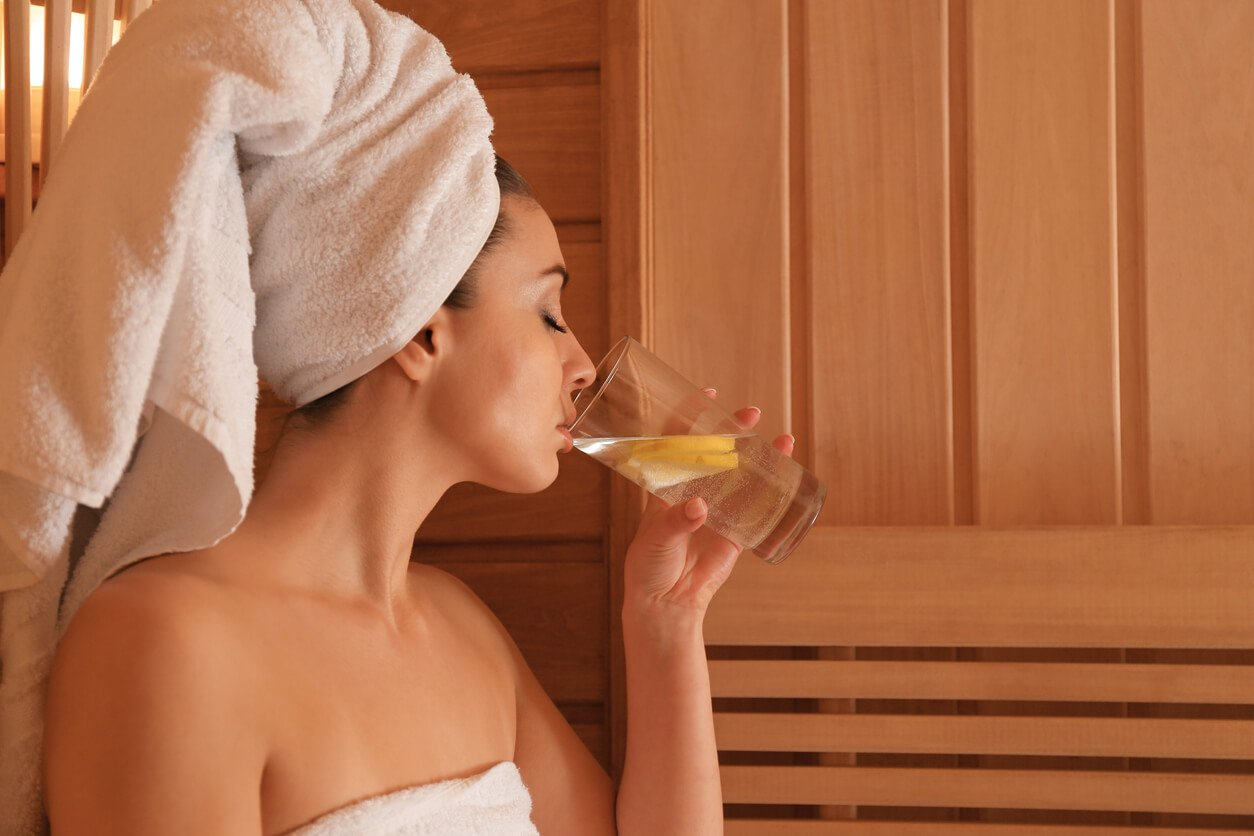 Young woman drinking cold water with lemon in sauna
