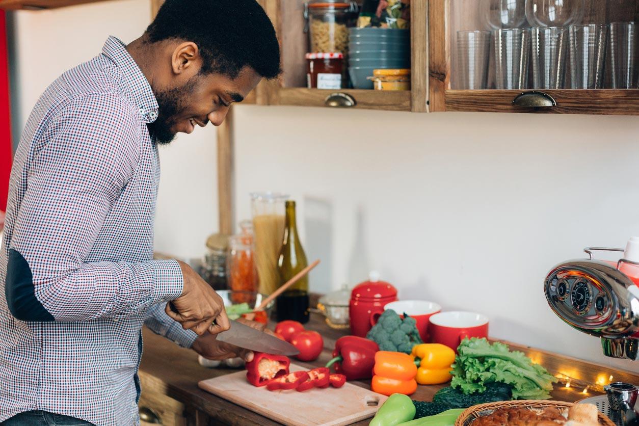 man cutting bell pepper in kitchen