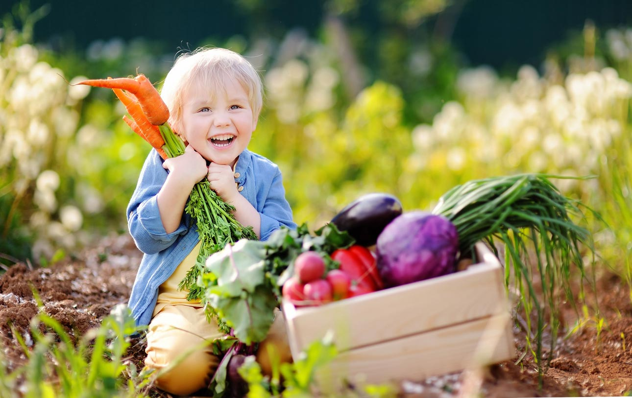 happy child holding carrot next to box of vegetables