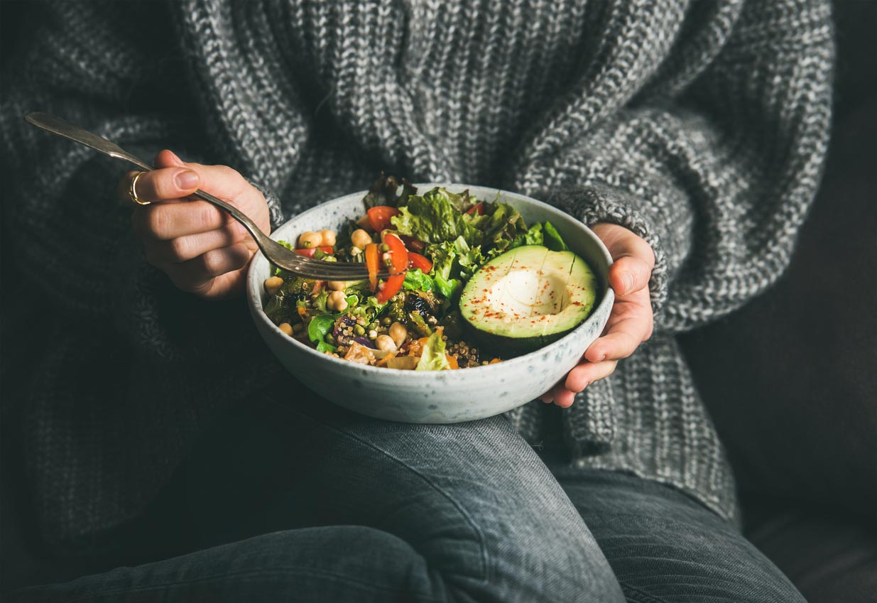 person in sweater holding bowl of greens
