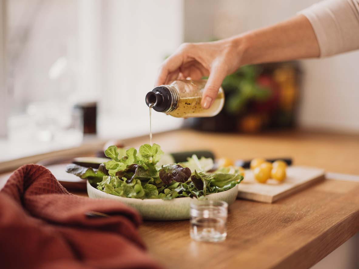 pouring vinegar dressing over salad