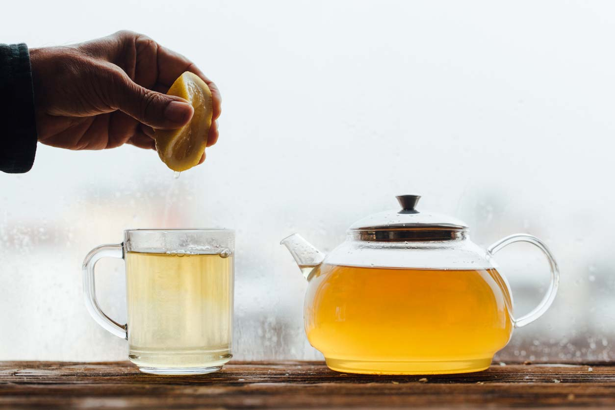 hand squeezing lemon with green tea pot and mug