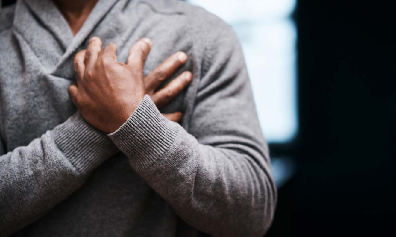 man of color with hands crossed holding chest near heart