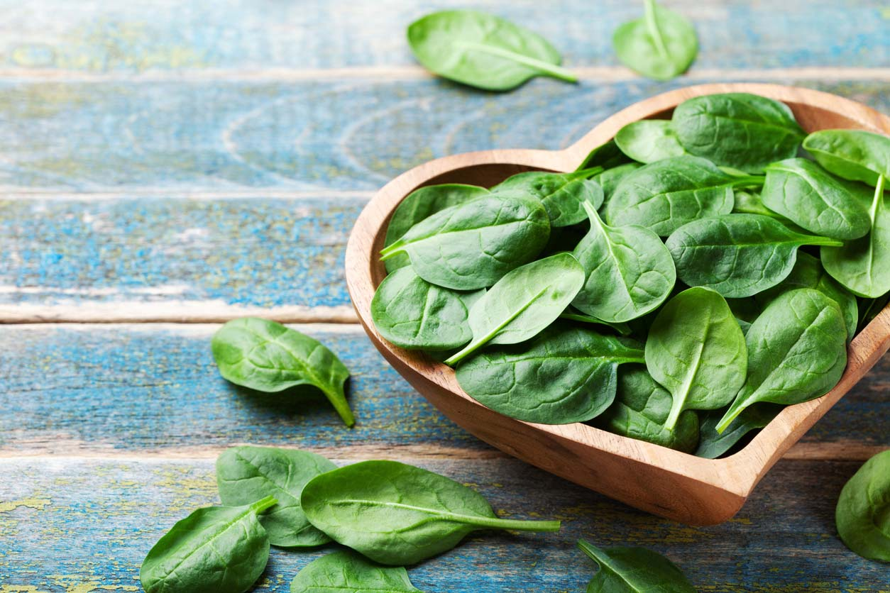 spinach in heart shaped bowl on table