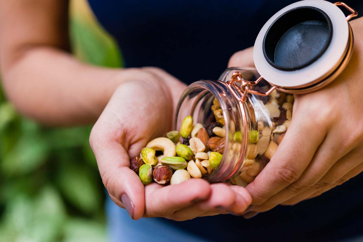 Person pouring mixed nuts out of jar into hand