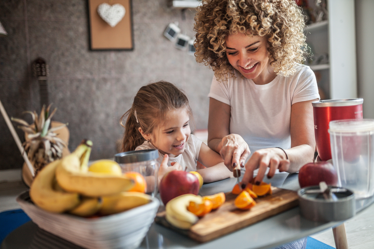 Young woman and daughter cutting up fruit on cutting board