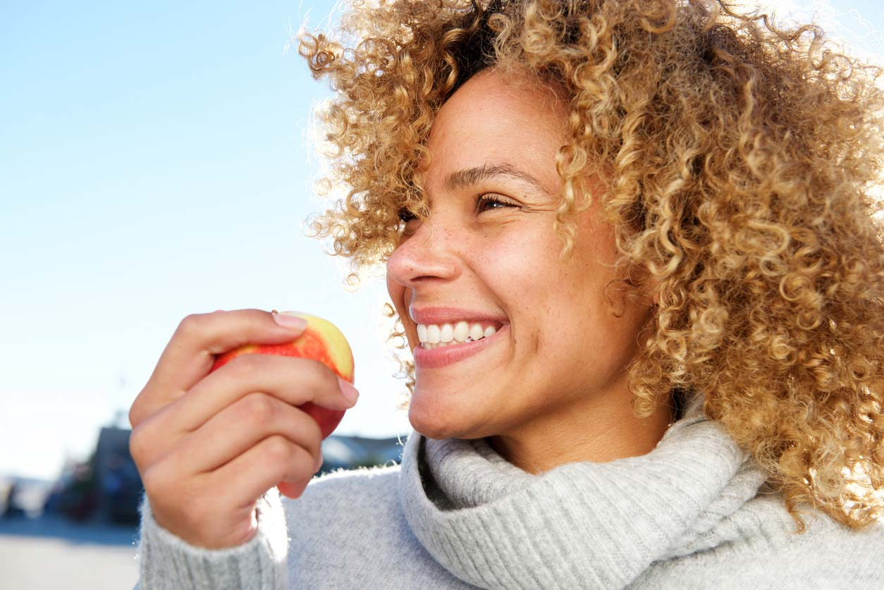 woman smiling and holding an apple