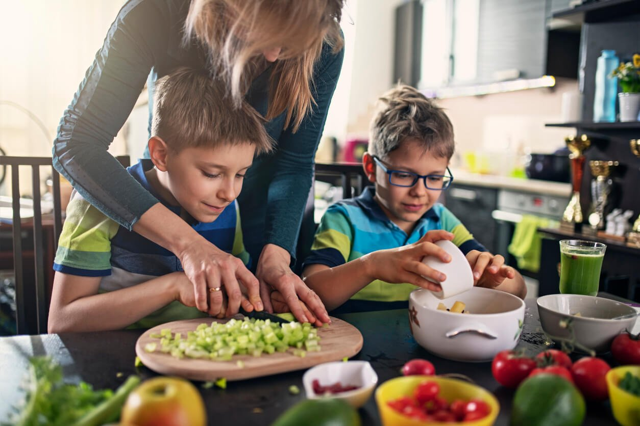 mother and sons making vegan salad at home - focusing on family nutrition