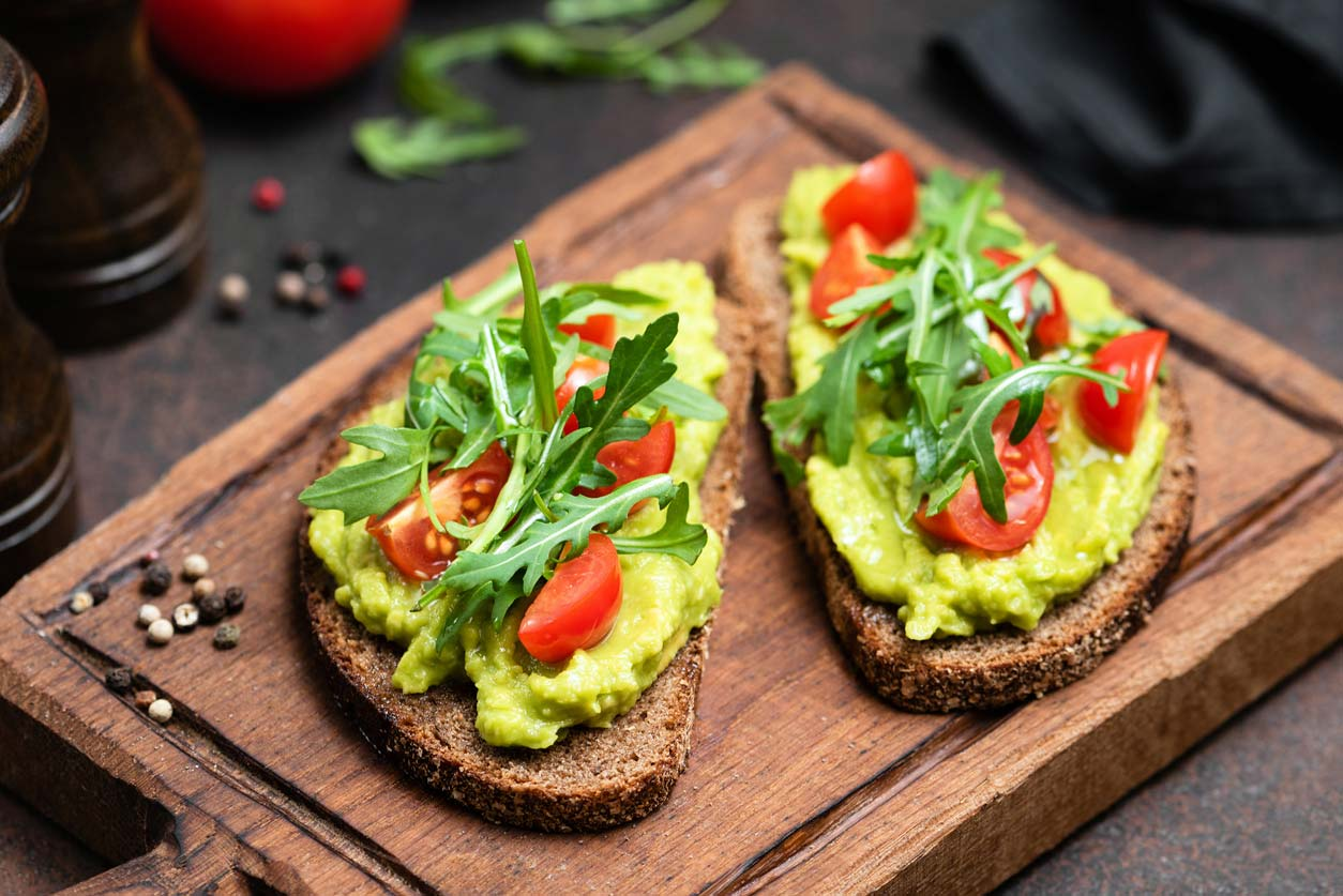 avocado toast with tomato and arugula garnish