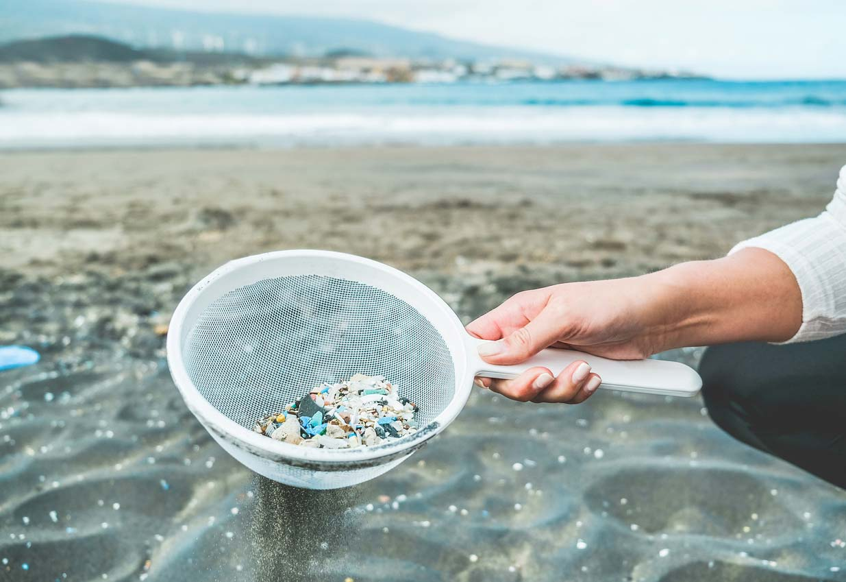 woman cleaning microplastics from sand