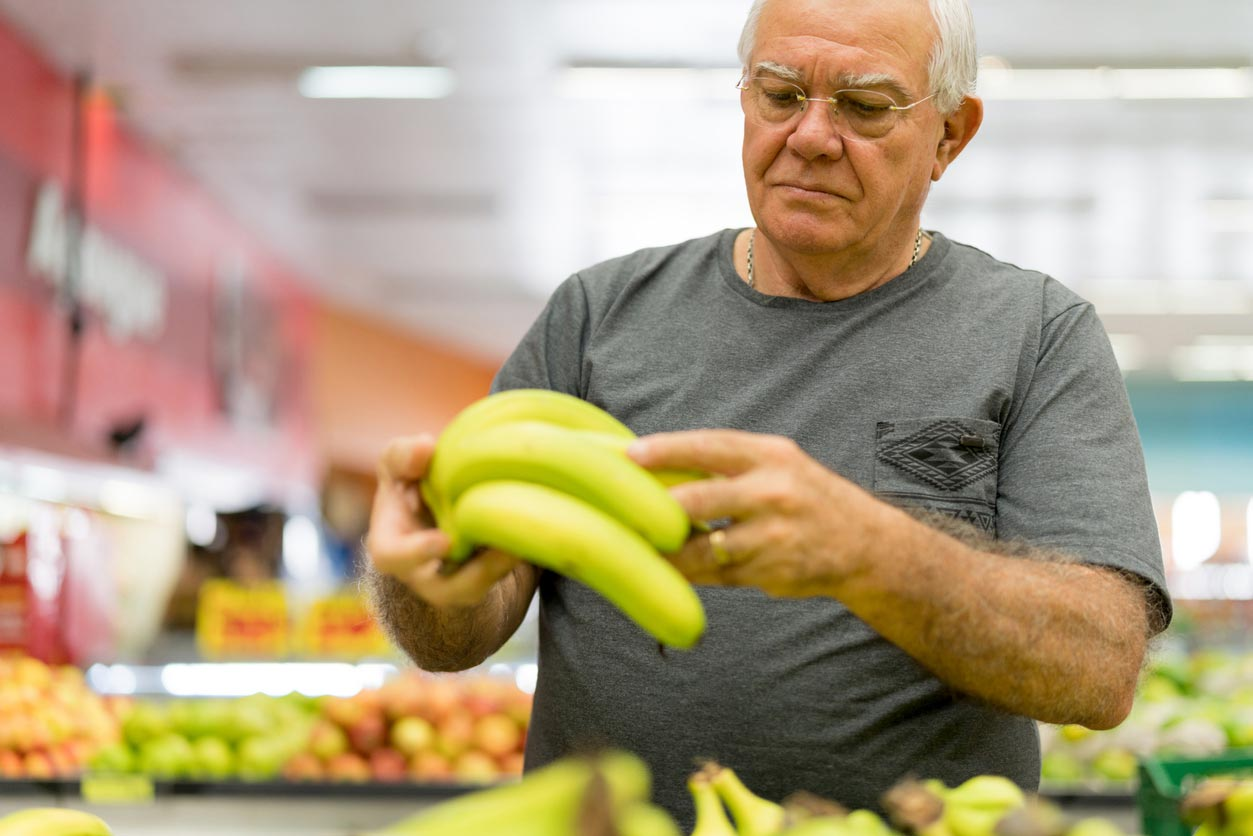 elderly man picking bananas produce section