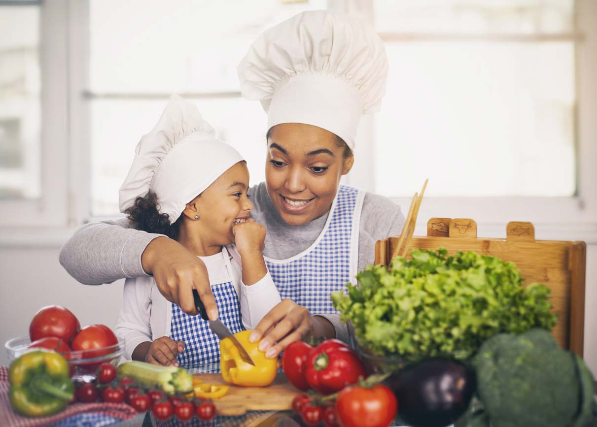 mother and daughter in chef hats making healthy food