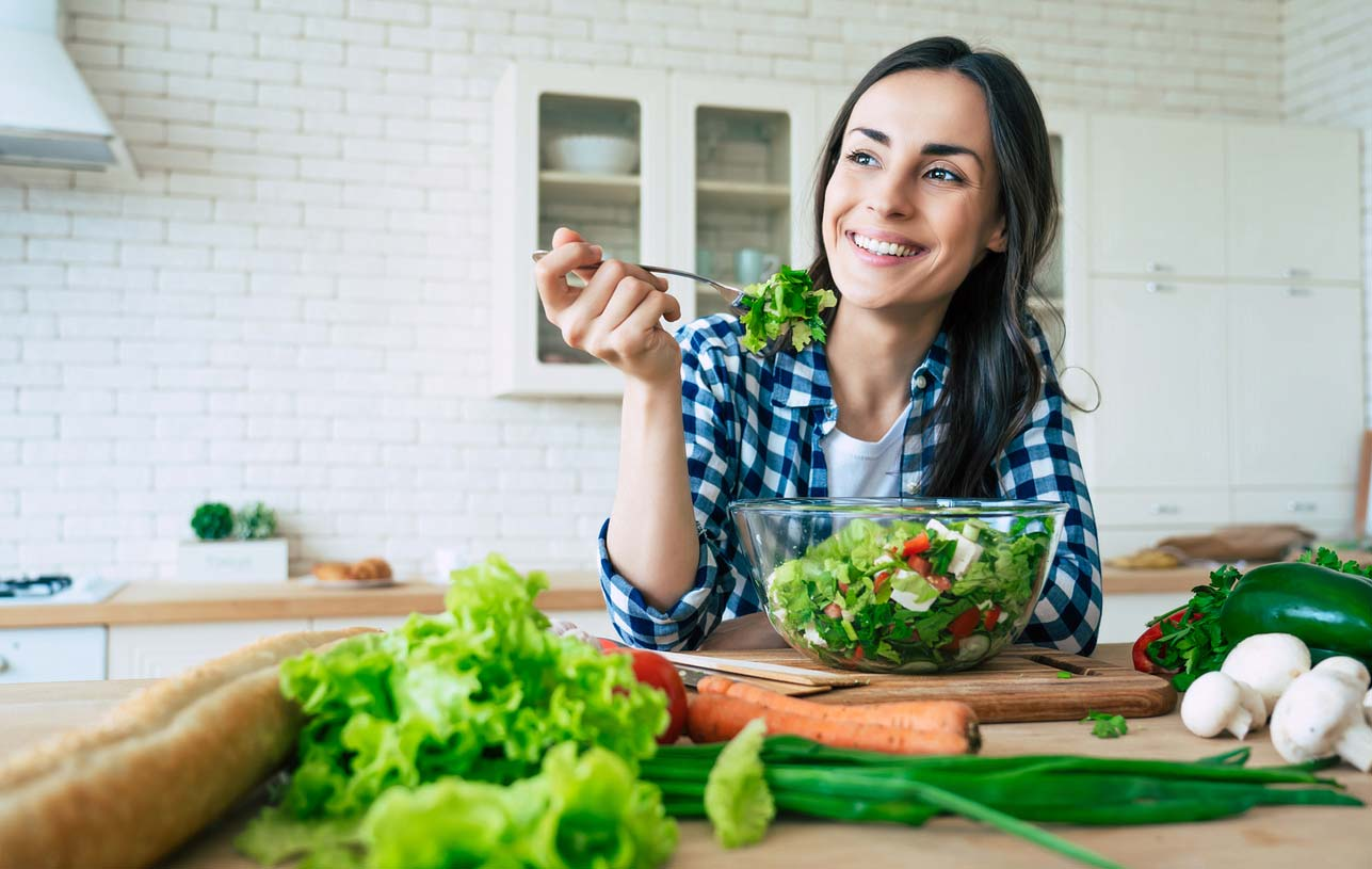 Woman enjoying a healthy salad in the kitchen