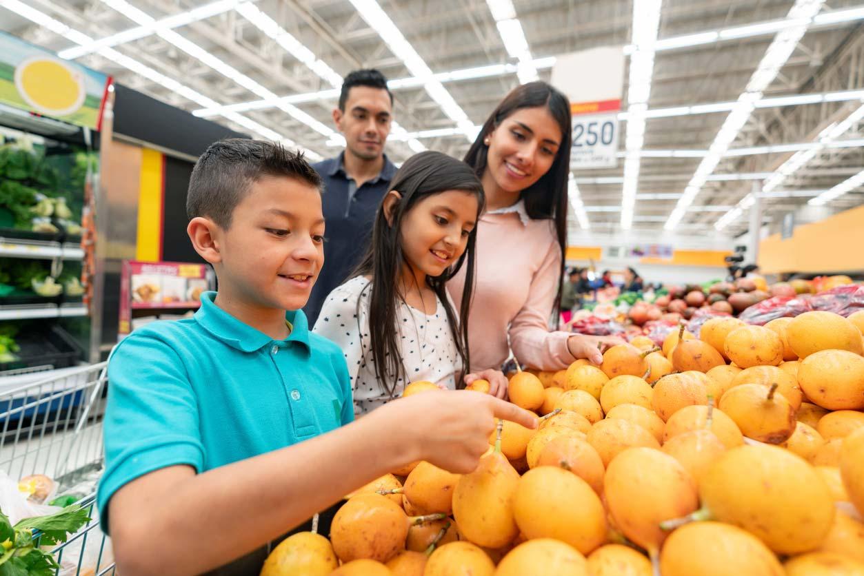 family at supermarket choosing fruits