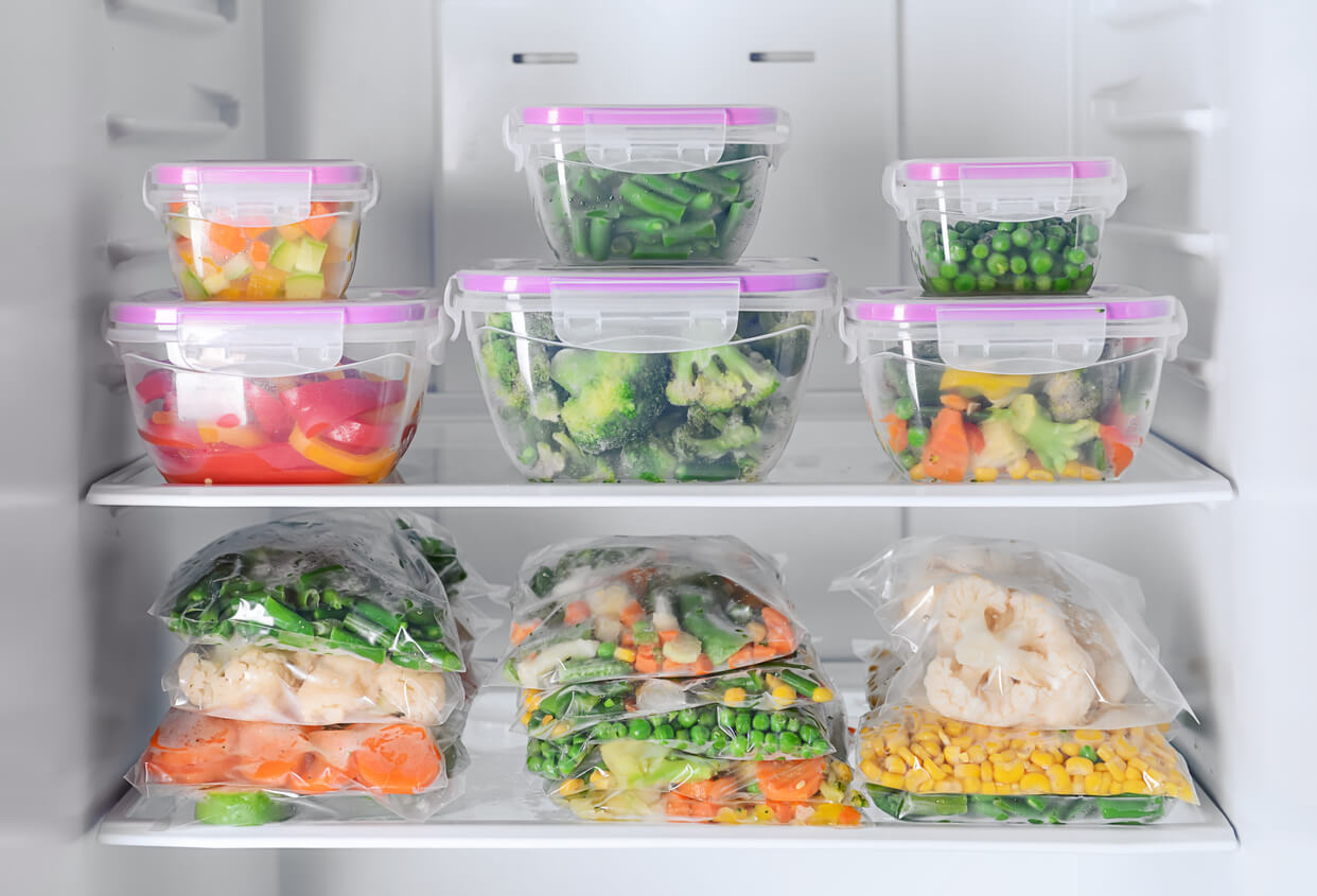 Plant-based meal prep with containers and plastic bags of fruits and vegetables in refrigerator