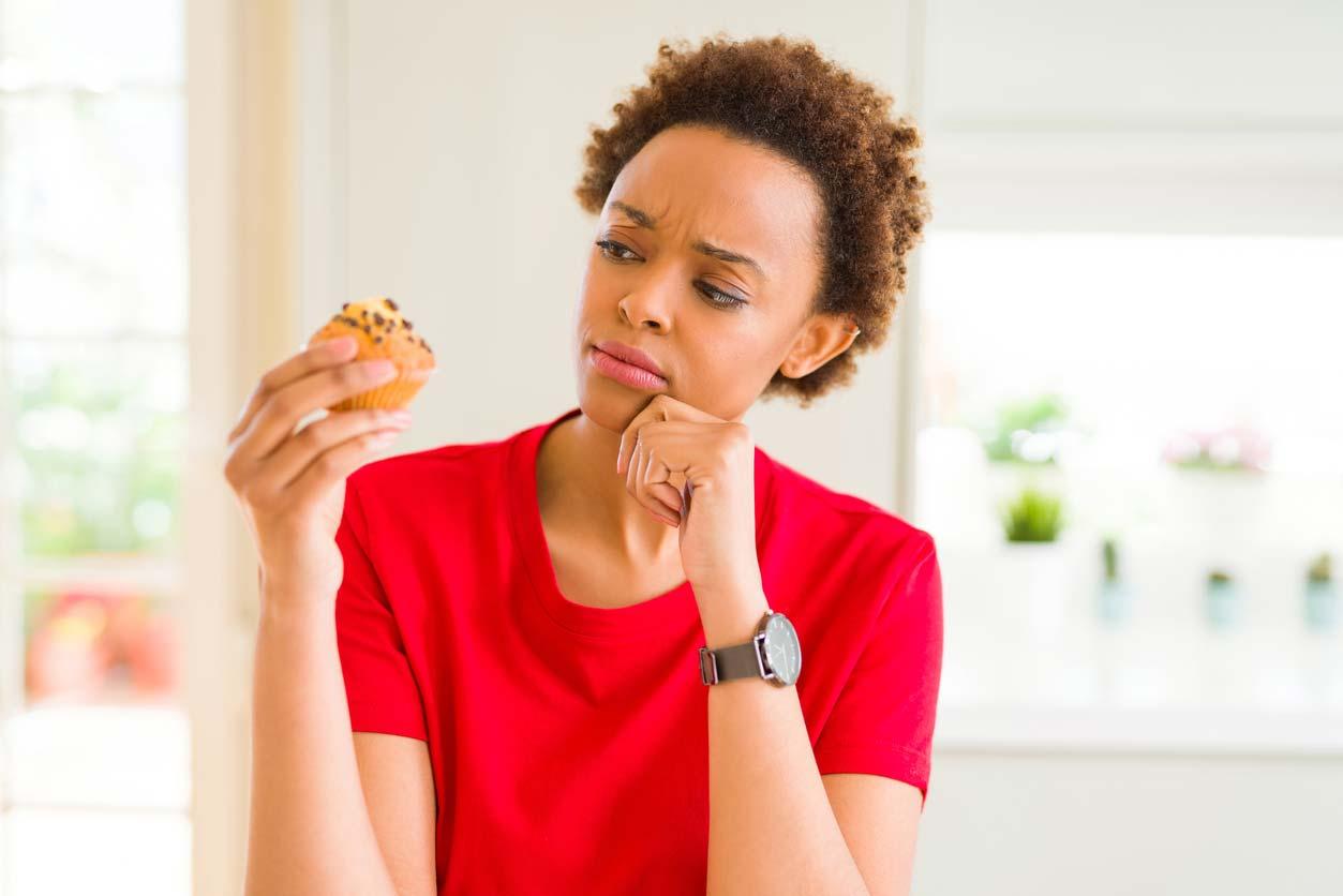 woman contemplating sugary treat