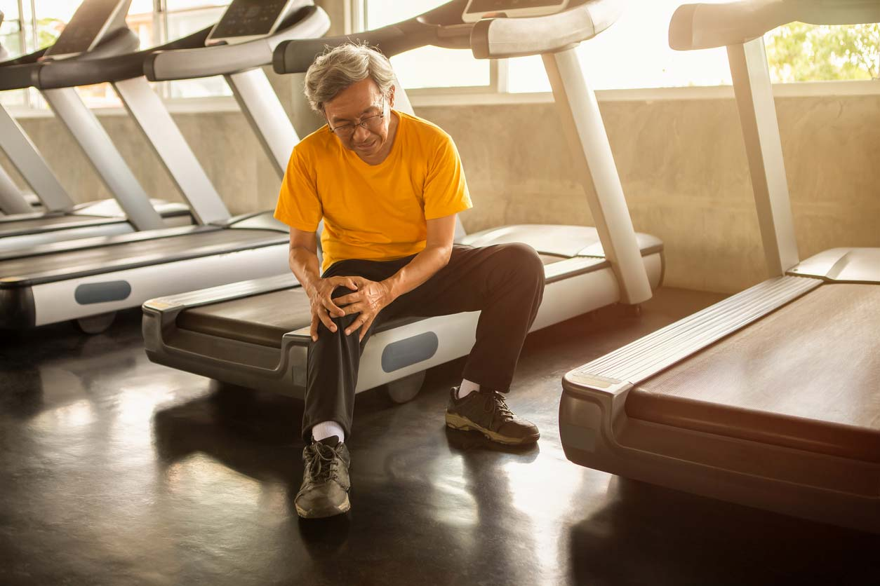 Vitamin D health benefits include bone health: Man holding his knee while sitting on treadmill