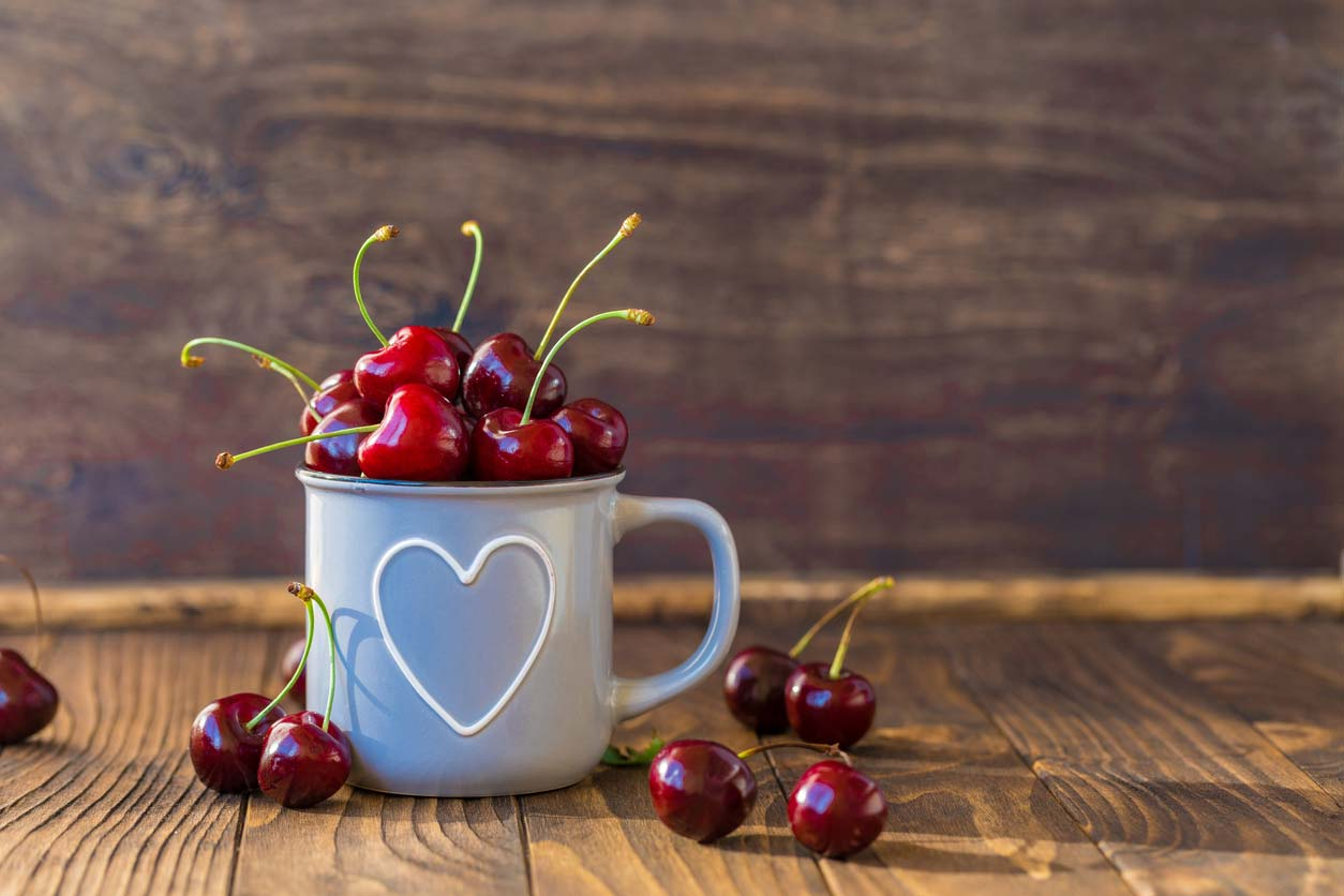cherries in a mug with a heart on it