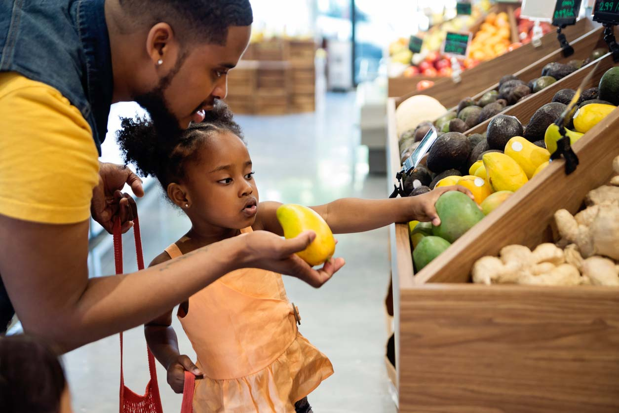father and daughter picking out mangoes from supermarket