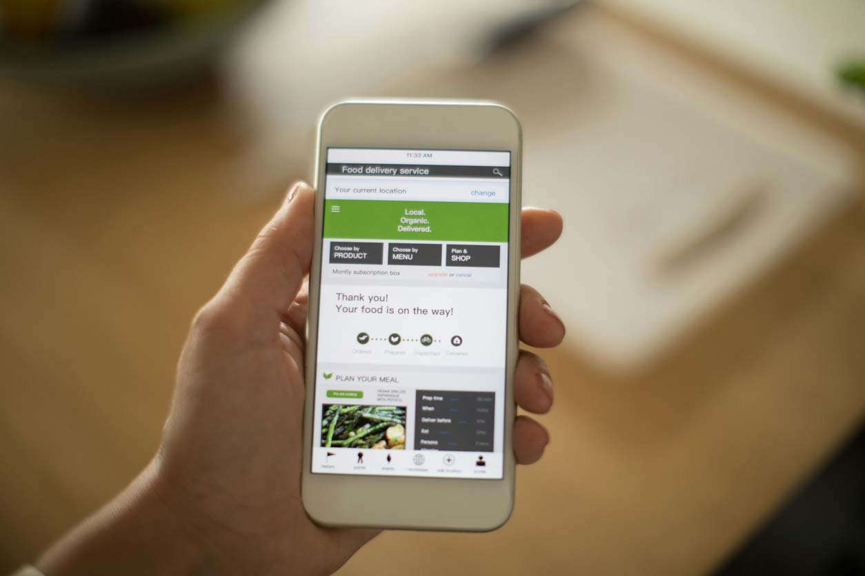 woman using plant-based meal delivery service on mobile app