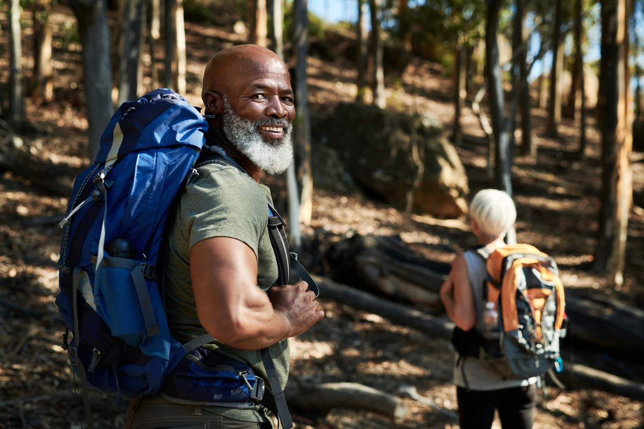 Elderly man and woman hiking on a trail - exercise can balance hormones naturally