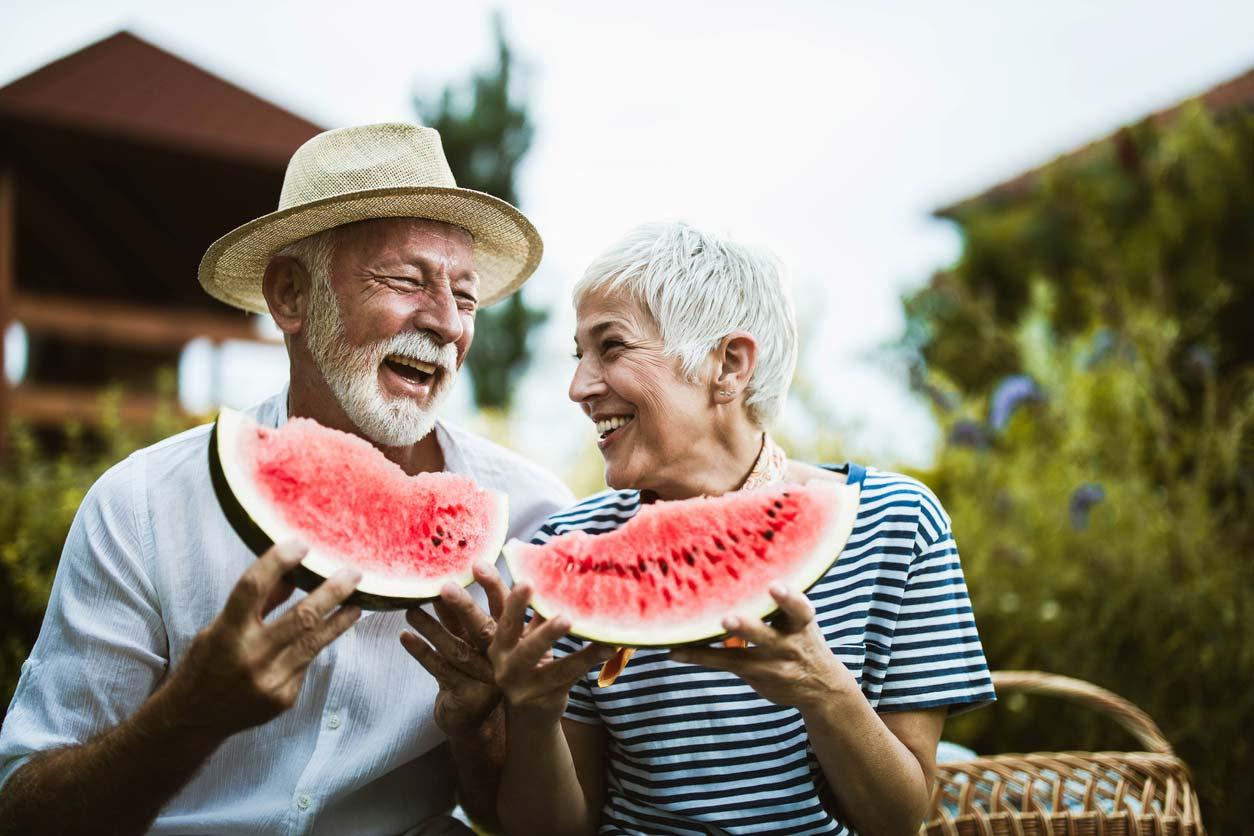 elderly couple enjoying watermelon together outside