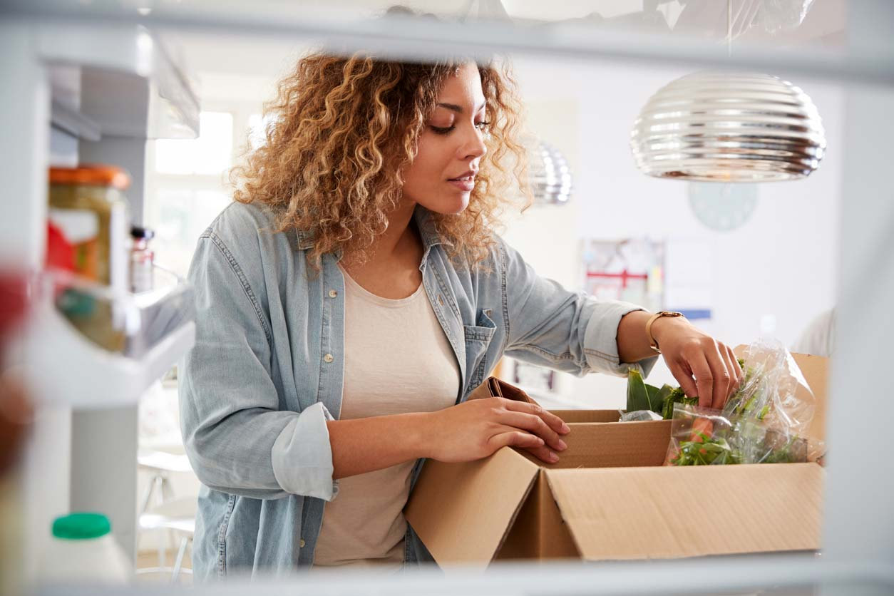 Woman unpacking her plant-based meal kit into fridge
