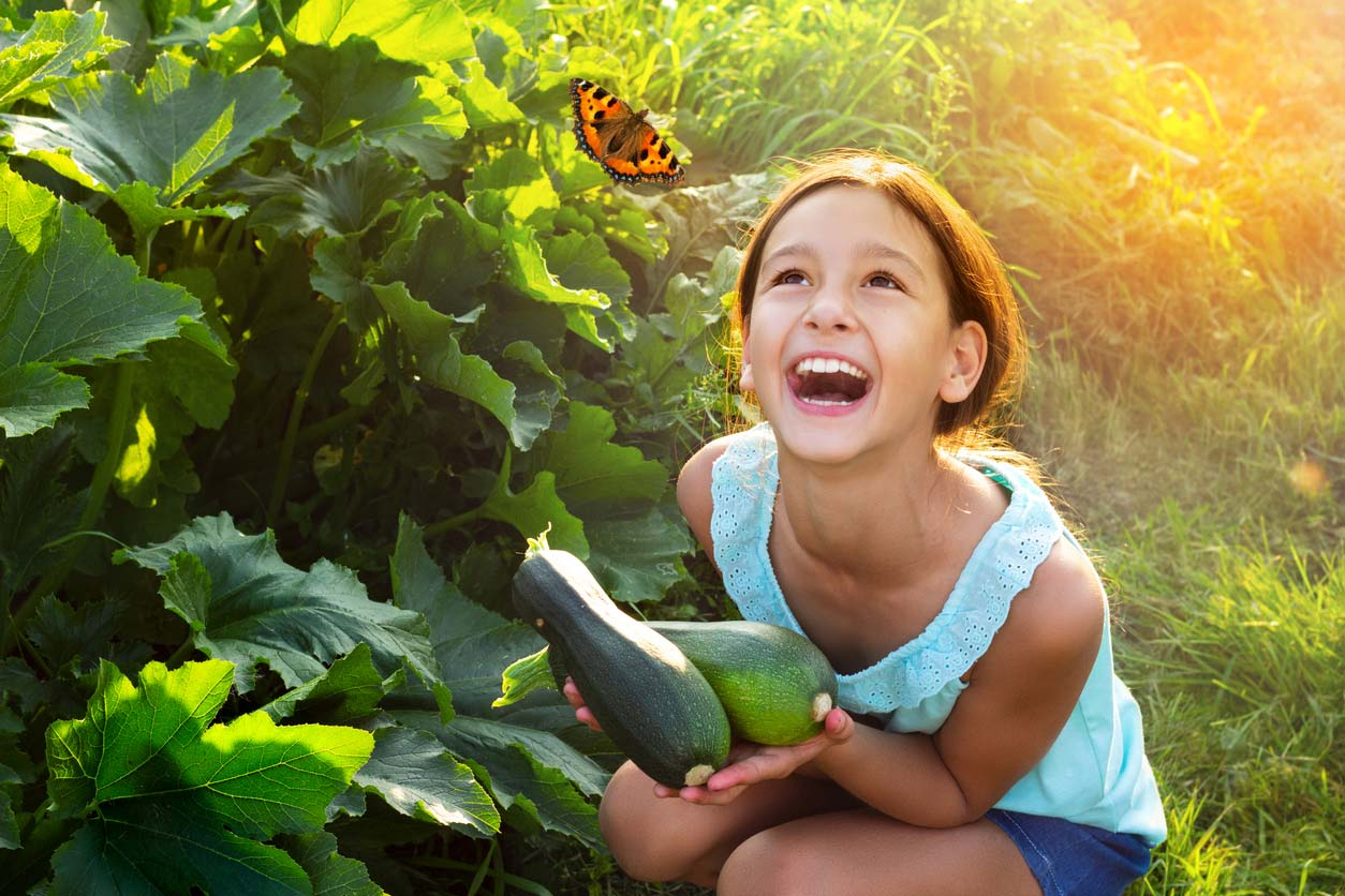 Young girl holding zucchini and looking at butterfly