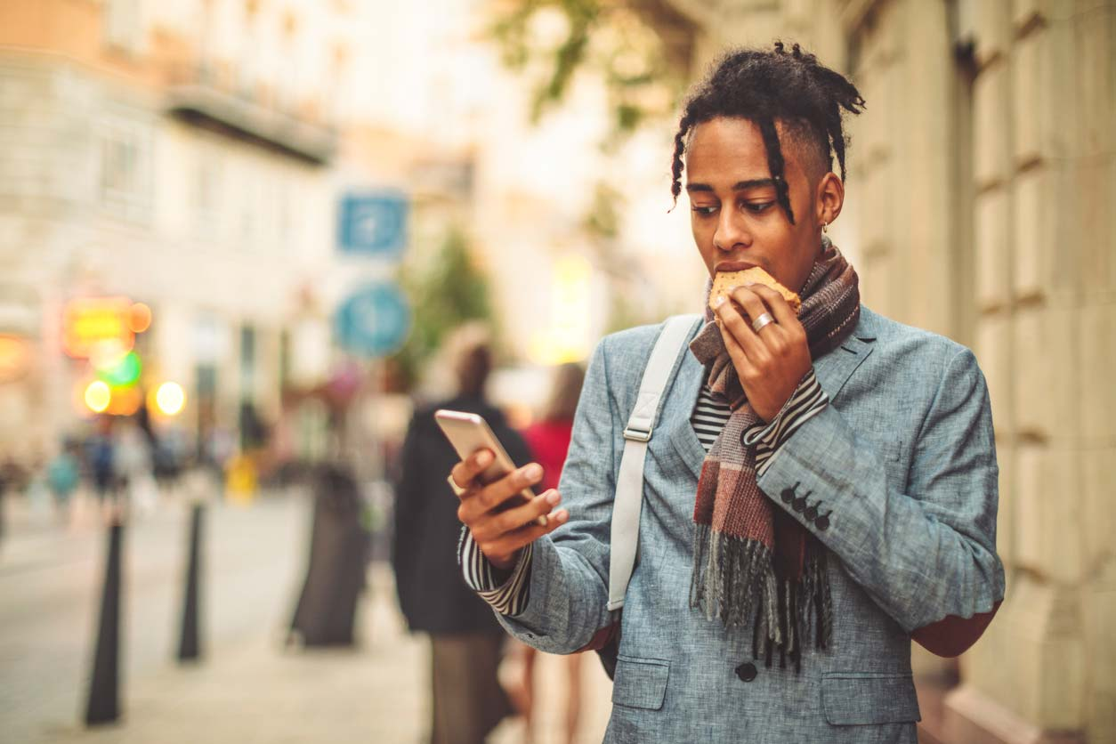 Person of color eating sandwich while holding phone on sidewalk