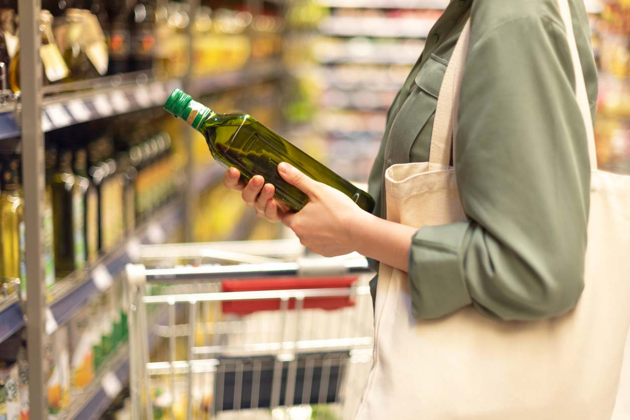Woman in grocery aisle holding oil bottle