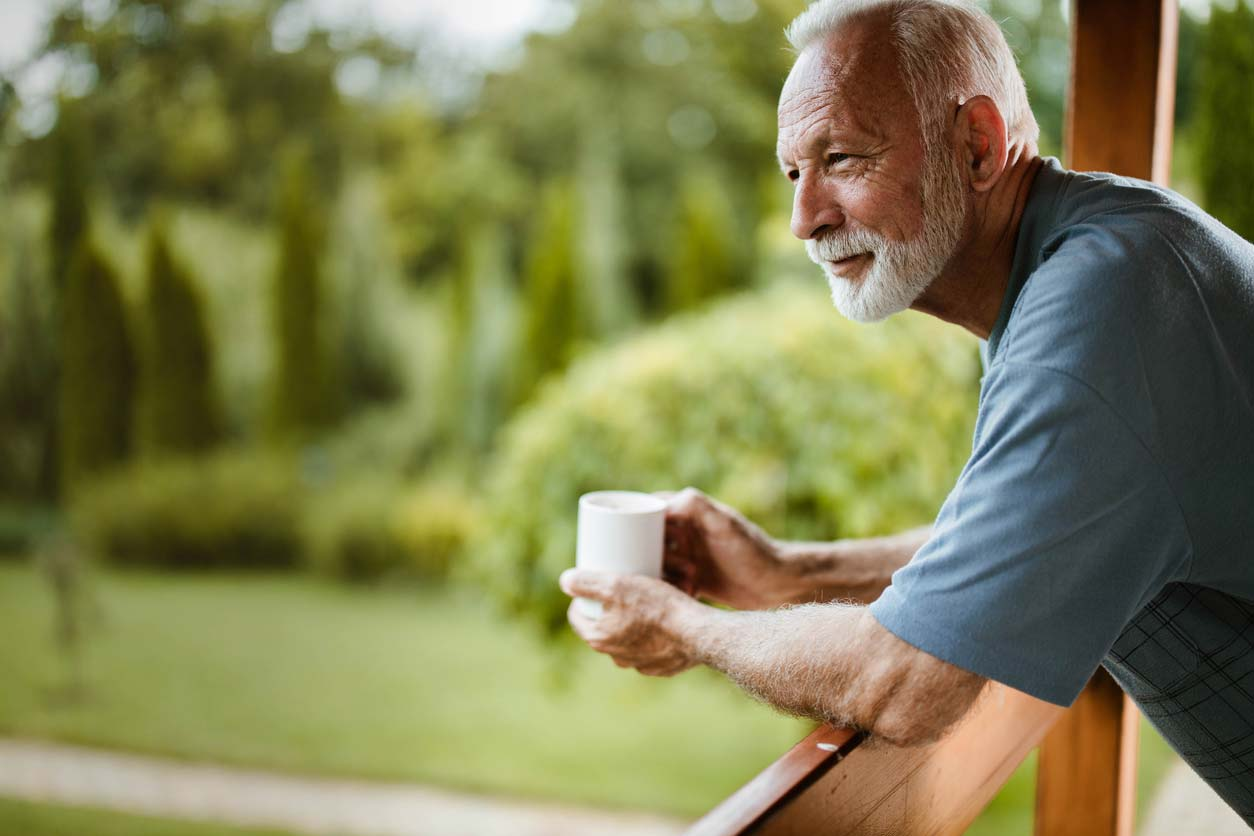elderly man enjoying nature with cup of coffee