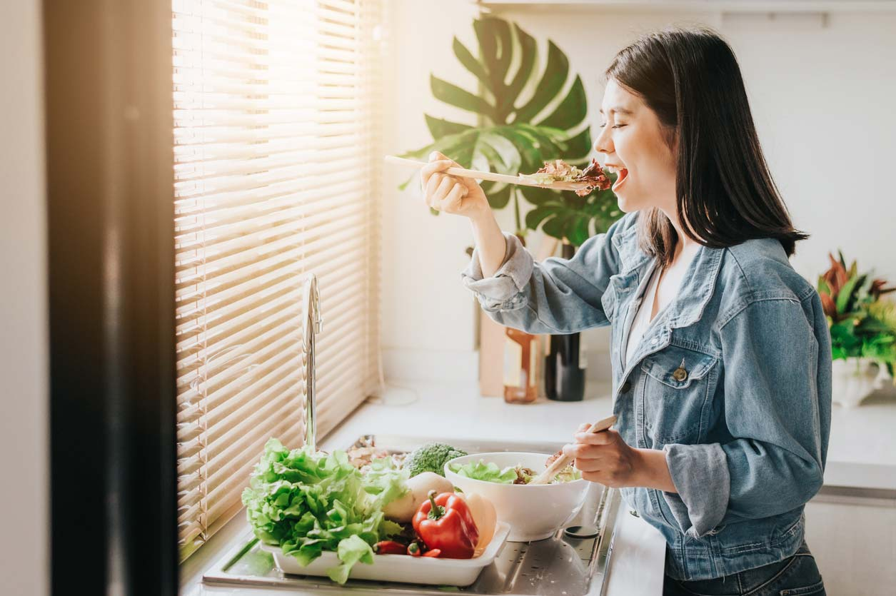 woman eating fresh vegetables while prepping healthy salads