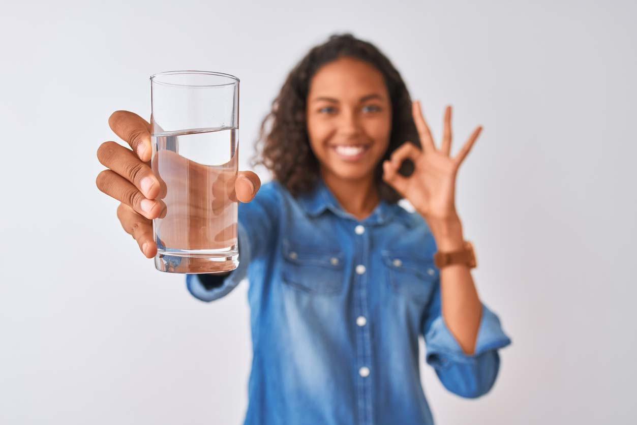 woman holding glass of water and giving okay hand gesture