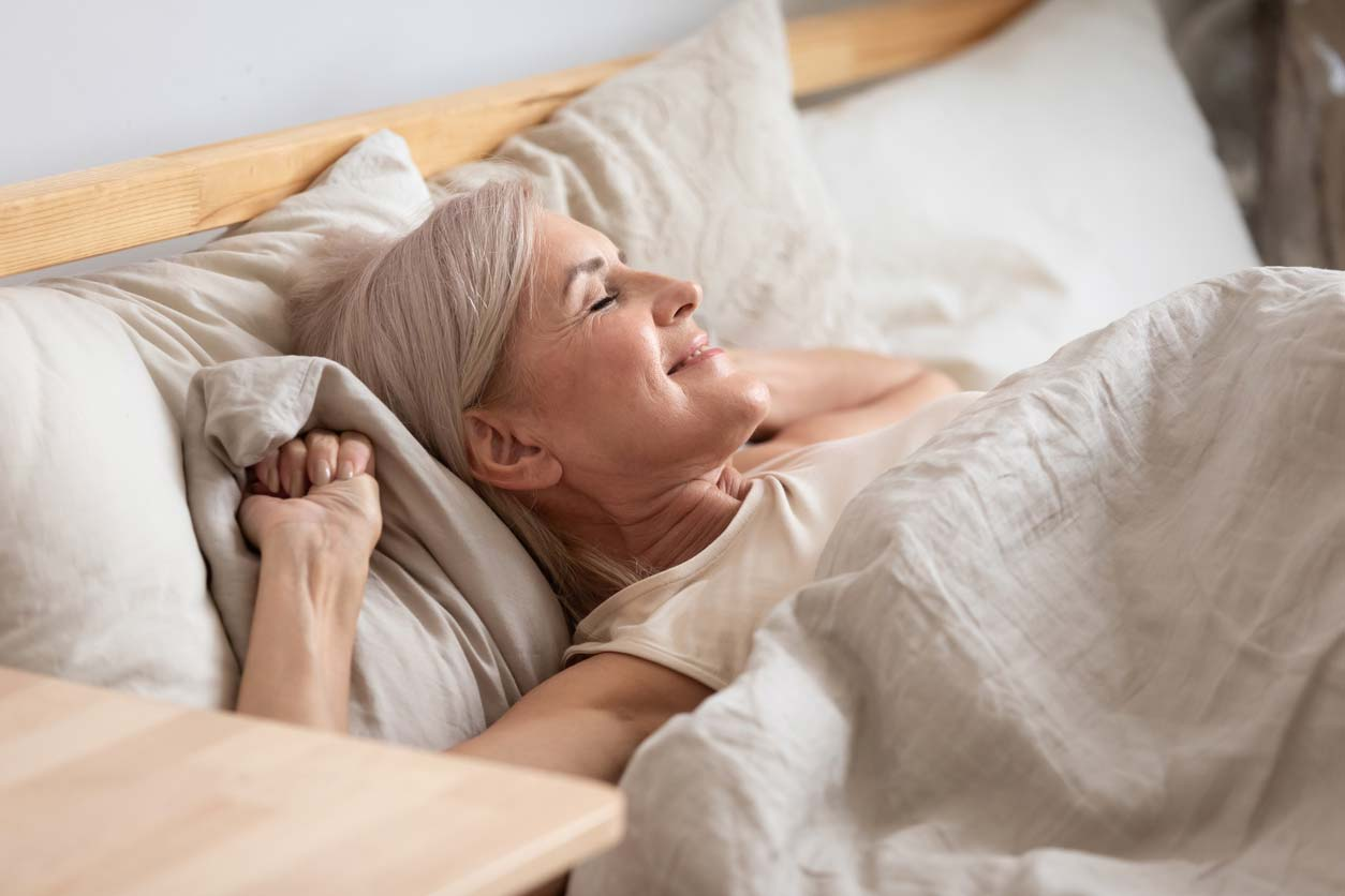 Senior woman stretching in bed