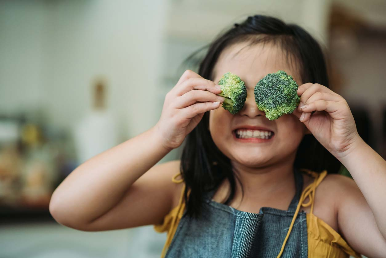 child holding broccoli in front of eyes