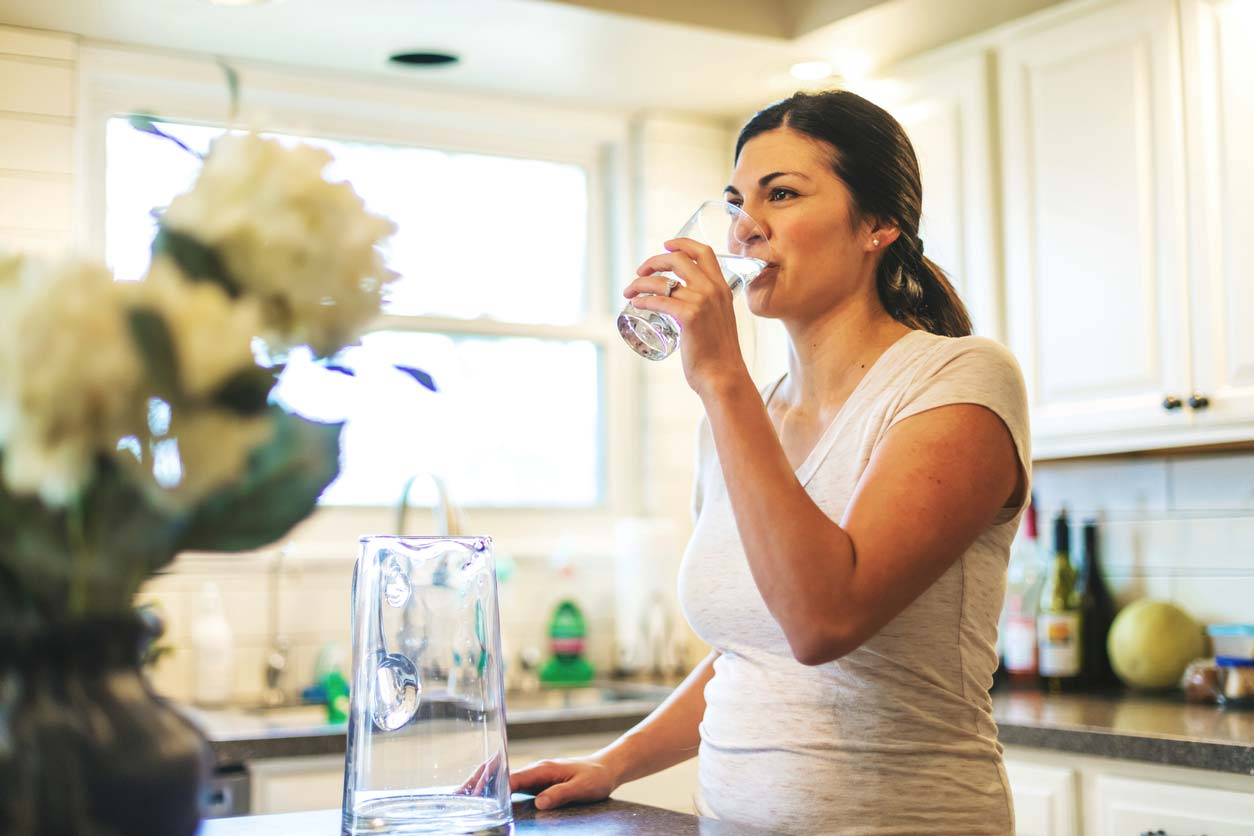 young woman drinking filtered water from glass