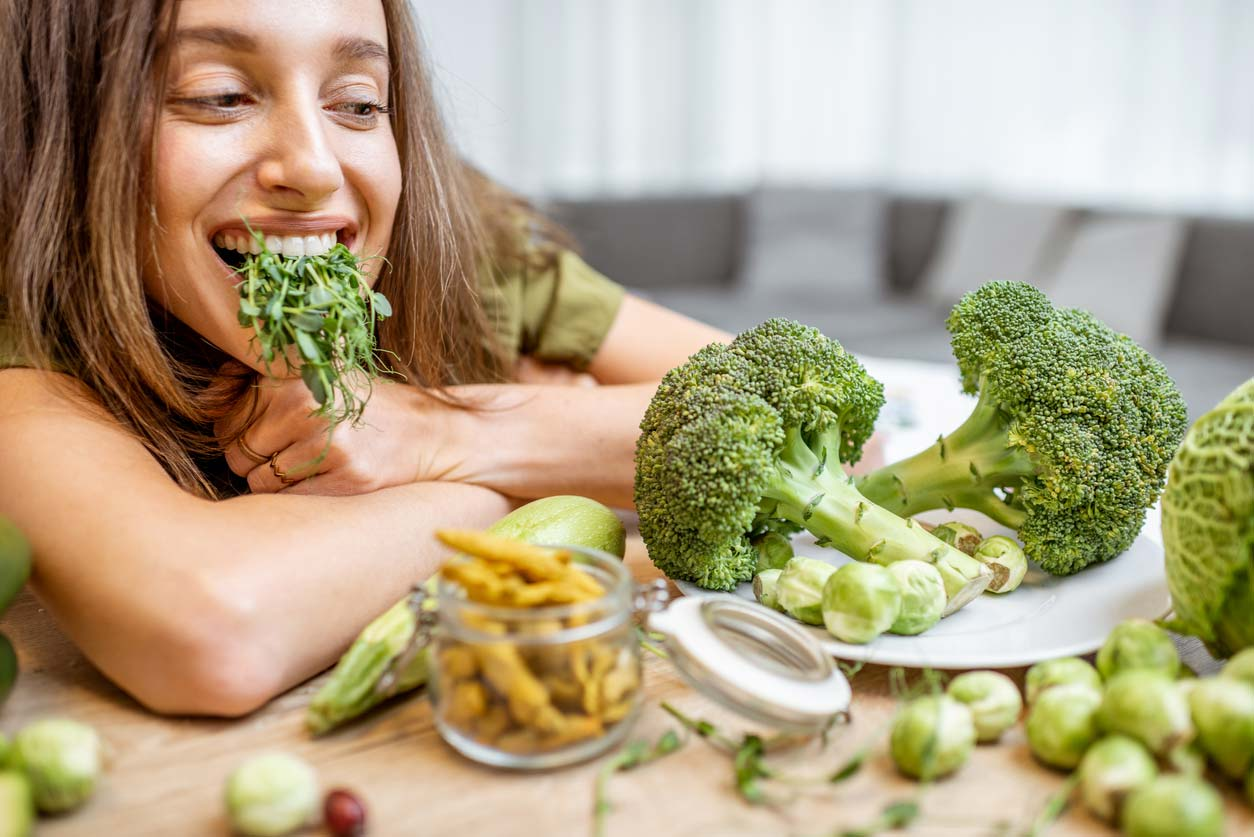 Woman with broccoli sprouts full of sulforaphane in her mouth