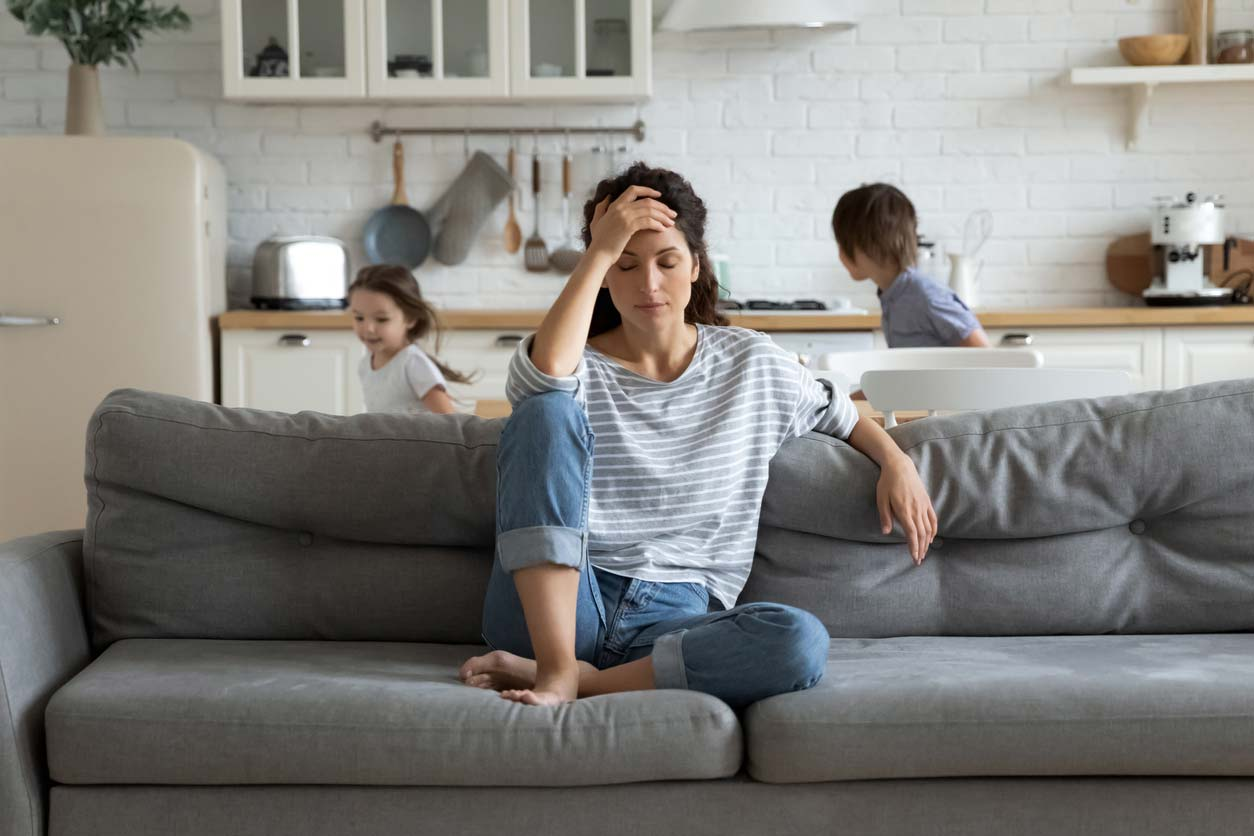 Exhausted mother sitting on couch while kids running in background - stress can impact hormones