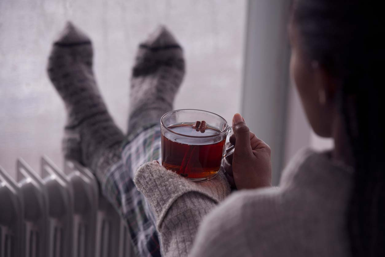 Woman holding a relaxing cup of tea and looking out a window