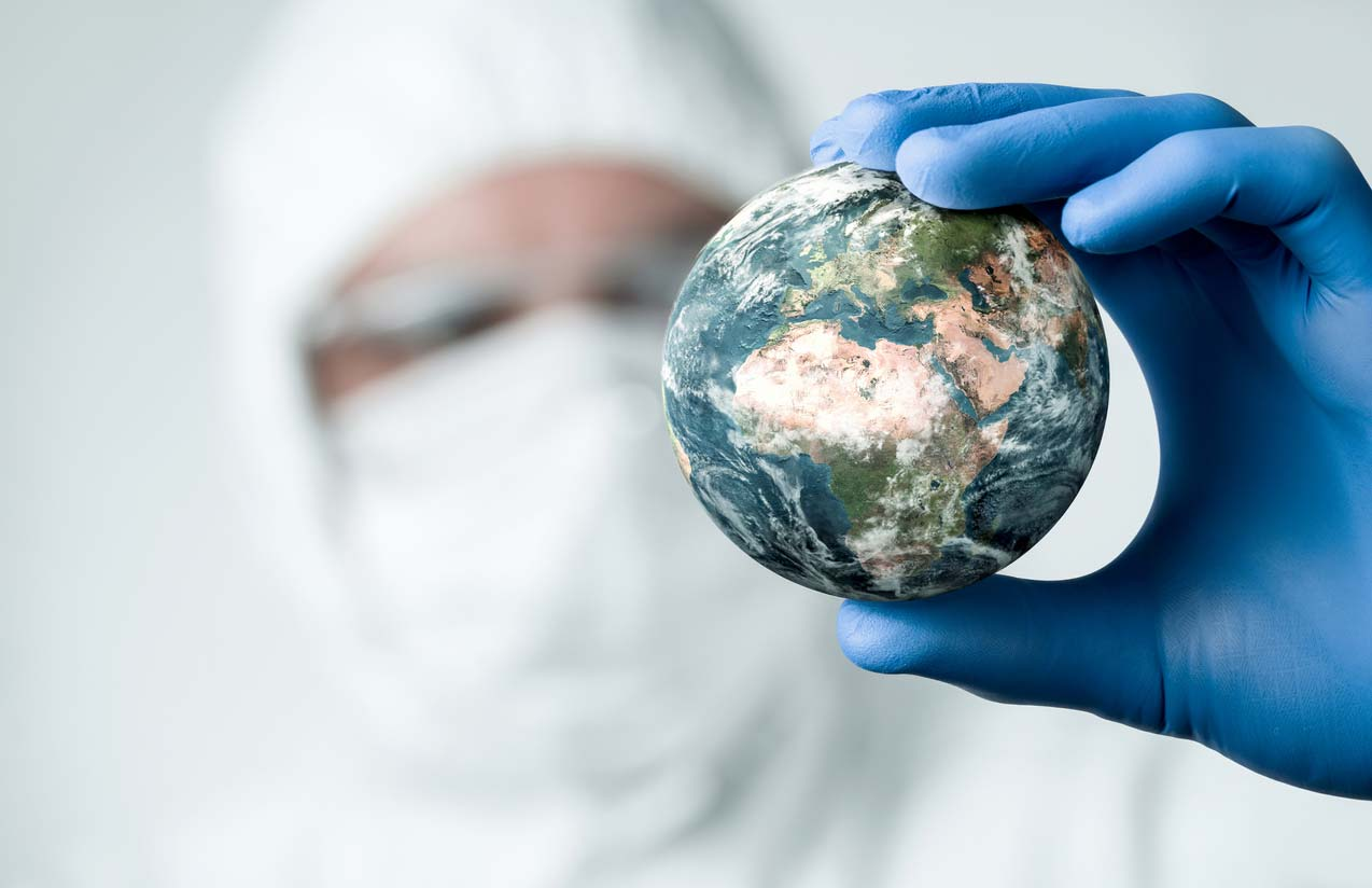 Person in ppe holding small model of the Earth