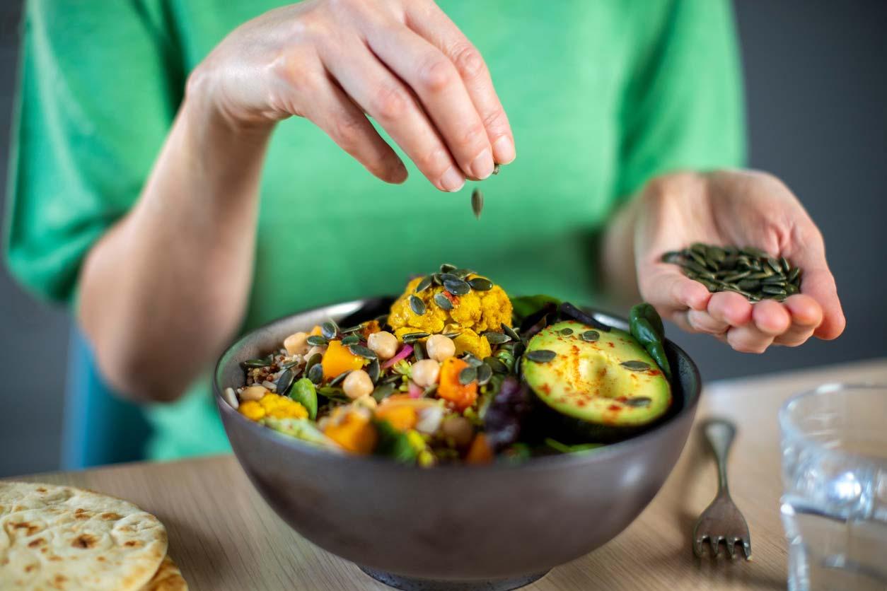 woman adding pumpkin seeds to vegan meal