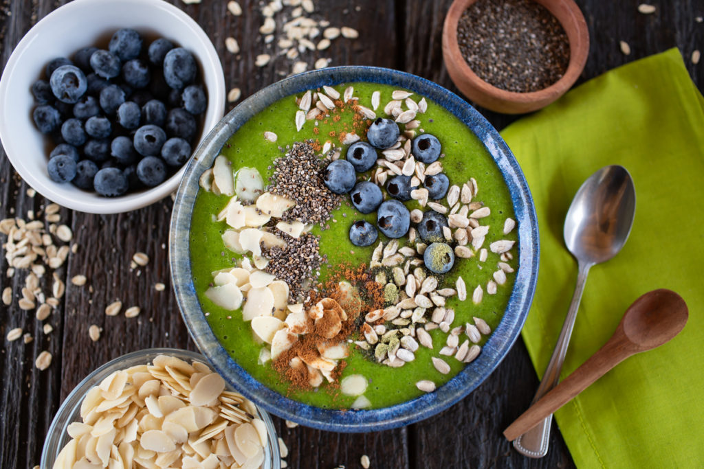 Healthy breakfast ideas: green smoothie bowl breakfast with berries, nuts, and seeds
