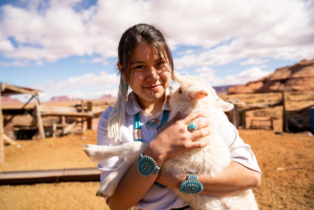 A Navajo girl holding a lamb on a reservation