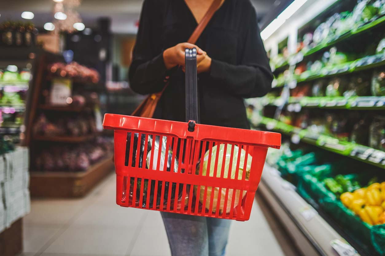 person holding shopping basket full of produce in grocery store