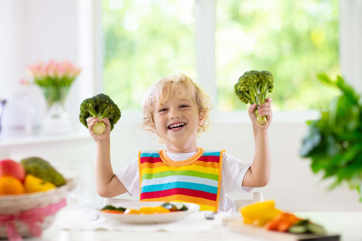 young child excitedly holding broccoli